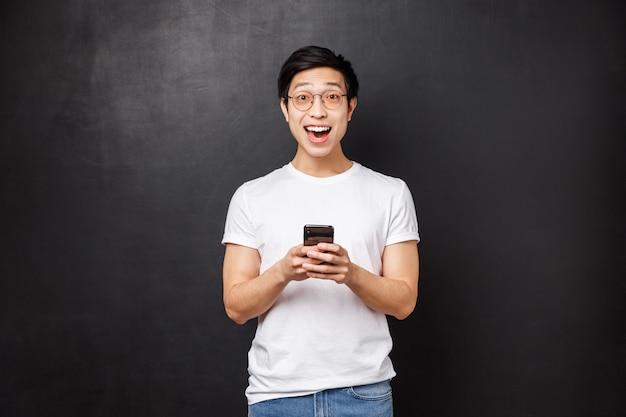 Koncepcja technologii, gadżetów i ludzi. super szczęśliwy uśmiechnięty pozytywny azjatycki facet w okularach i koszulce, reaguje rozbawiony i zastanawia się nad niesamowitymi wiadomościami otrzymanymi za pośrednictwem poczty elektronicznej, trzyma kamerę wyglądającą na telefon