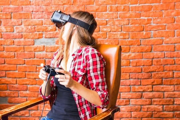 Koncepcja technologii, gier, rozrywki i ludzi - szczęśliwy młody człowiek z zestawem słuchawkowym wirtualnej rzeczywistości lub okularami 3d z kontrolerem gamepad gra wyścigowa gra wideo w domu