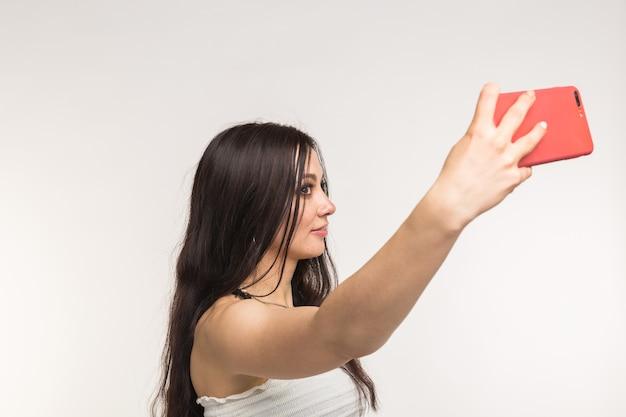 Koncepcja technologii i ludzi - młoda kobieta robi selfie zdjęcie i uśmiechając się na białym tle.