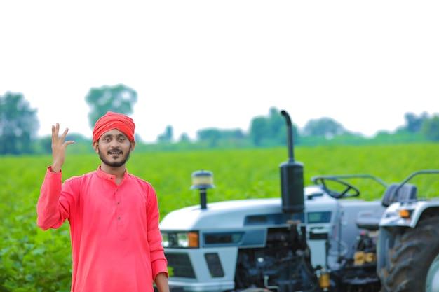 Koncepcja technologii i ludzi, portret młodego indyjskiego rolnika z ciągnikiem