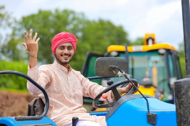 Koncepcja technologii i ludzi, portret młodego rolnika indyjskiego z ciągnikiem
