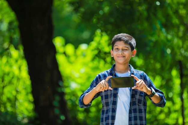 Koncepcja technologii i ludzi - uśmiechnięty nastolatek w niebieskiej koszuli przedstawiający smartfon z pustym ekranem