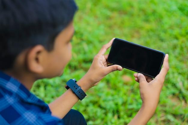 Koncepcja technologii i ludzi - uśmiechnięty nastolatek w niebieskiej koszuli za pomocą smartfona