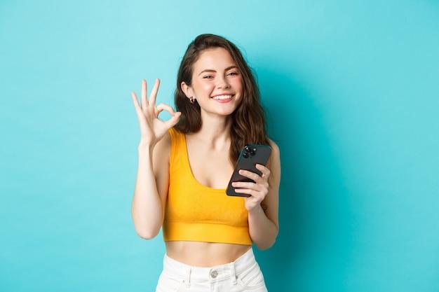Koncepcja technologii i stylu życia. piękna dziewczyna ze szczęśliwym uśmiechem, pokazując znak zgody, powiedz tak, trzymając smartfon, stojąc na niebieskim tle.