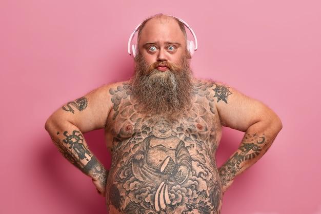 Koncepcja technologii i stylu życia. poważny, pewny siebie pulchny mężczyzna nosi słuchawki, słucha muzyki, ma wytatuowane ciało, gruby brzuch, gęstą brodę, pozuje na różowej ścianie, znalazł świetną playlistę