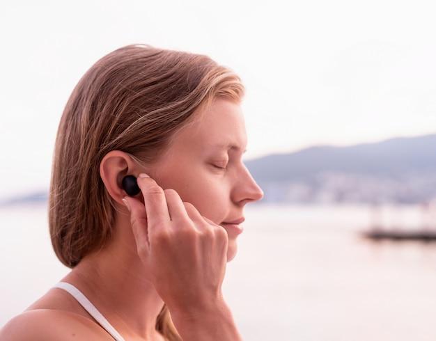 Koncepcja technologii. kobieta korzystająca z bezprzewodowych słuchawek, nad morzem w tle