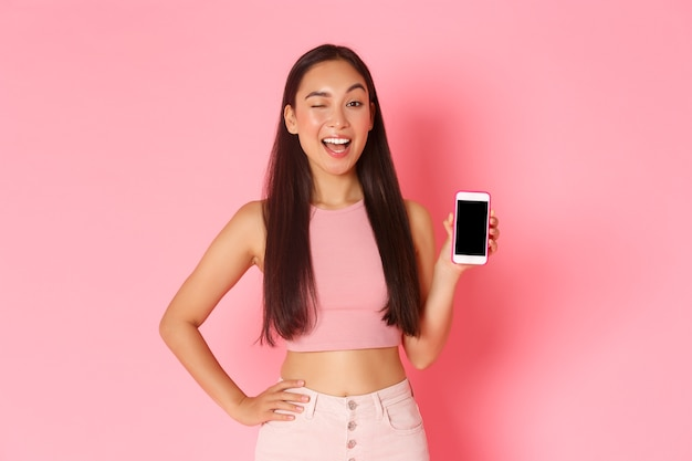 Koncepcja technologii, komunikacji i stylu życia online. portret zalotnej, mrugającej azjatki zachęca do pobrania aplikacji, obejrzenia podcastu lub sklepu internetowego, pokazującego ekran smartfona.