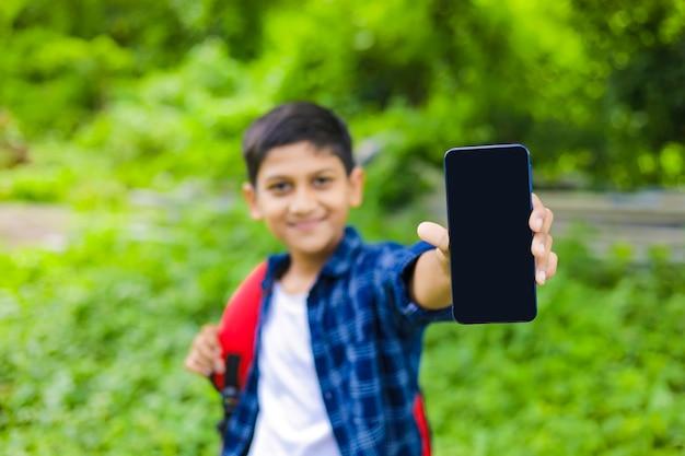 Koncepcja technologii: ładny indyjski mały chłopiec trzyma torbę i pokazuje smartfon