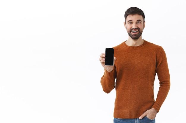 Koncepcja technologii, ludzi i komunikacji. portret entuzjastycznie przystojnego brodatego mężczyzny, pokazującego smartfona i uśmiechniętego szczęśliwego, facet poleca aplikację na ekranie telefonu komórkowego