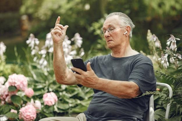 Koncepcja technologii, ludzi i komunikacji. starszy mężczyzna w lato park. grangfather używa telefonu.