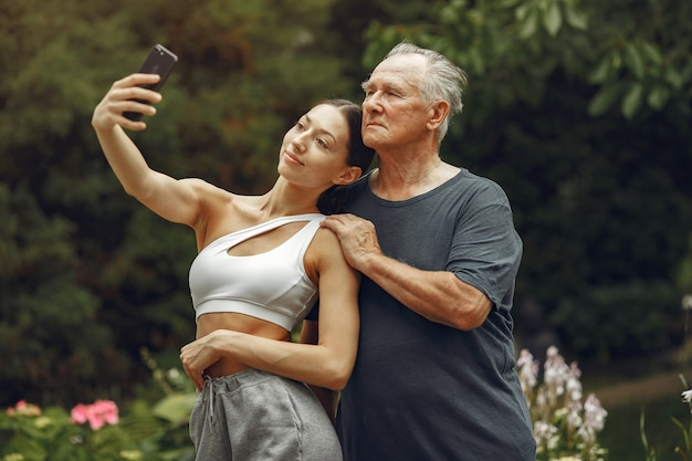 Koncepcja technologii, ludzi i komunikacji. starszy mężczyzna w lato park. grangfather z wnuczką.