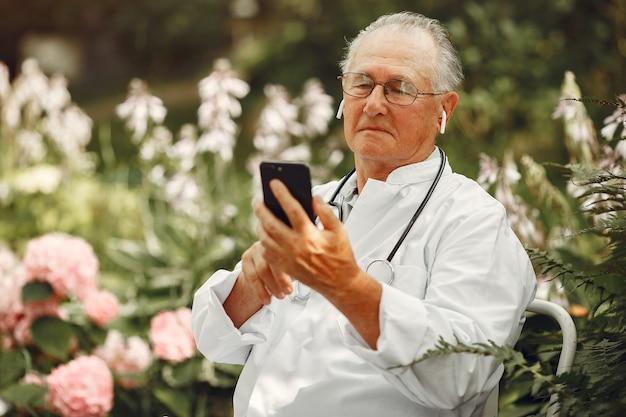 Koncepcja technologii, ludzi i komunikacji. starszy mężczyzna w lato park. lekarz za pomocą telefonu.