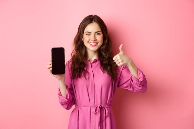 Koncepcja technologii. młoda dziewczyna w sukience pokazuje ekran swojego smartfona i kciuki do góry, przytakuje z aprobatą, chwali dobrą aplikację, stoi nad różową ścianą.