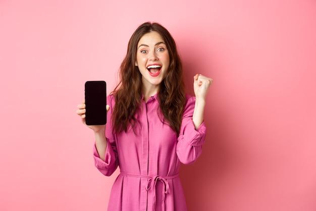 Koncepcja technologii. podekscytowana dziewczyna pokazuje ekran telefonu komórkowego i krzyczy z radości i szczęścia, wygrywając pieniądze online, osiągając dzienny cel w aplikacji na smartfony, różowa ściana.