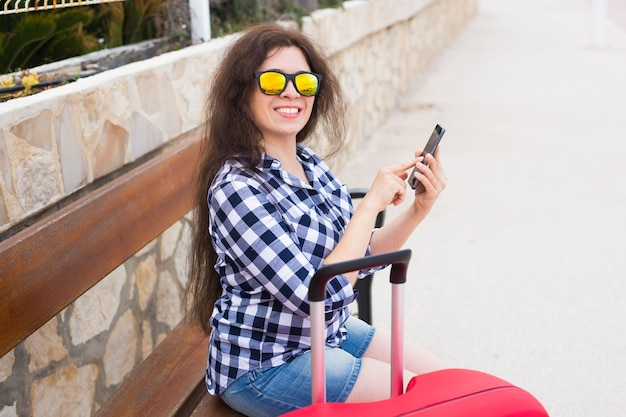Koncepcja technologii, podróży i ludzi - młoda kobieta siedzi na ławce w słonecznych okularach i pisze na telefonie.