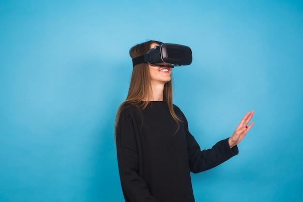 Koncepcja technologii, rzeczywistości wirtualnej, rozrywki i ludzi - szczęśliwa młoda kobieta z zestawem słuchawkowym wirtualnej rzeczywistości lub okularami 3d.