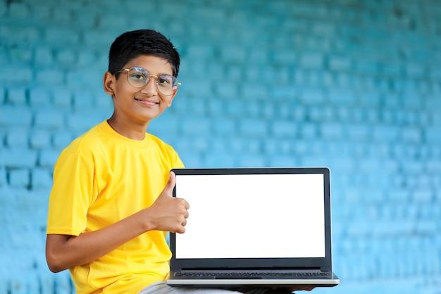 Koncepcja technologii: śliczny indyjski mały chłopiec w szkole używający laptopa i pokazujący aprobaty