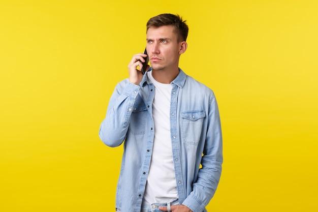 Koncepcja technologii, stylu życia i reklamy. poważnie wyglądający mężczyzna słuchający osoby na telefonie, mający ważną rozmowę biznesową, marszczący brwi i odwracający wzrok podczas dzwonienia do przyjaciela.