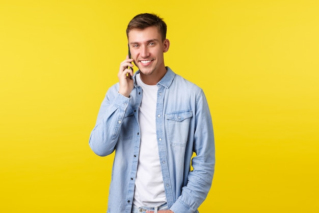Koncepcja technologii, stylu życia i reklamy. przystojny nowoczesny młody człowiek w ubranie, dzwoniąc do przyjaciela, rozmawiając przez telefon komórkowy i uśmiechając się do kamery, stojąc na żółtym tle.