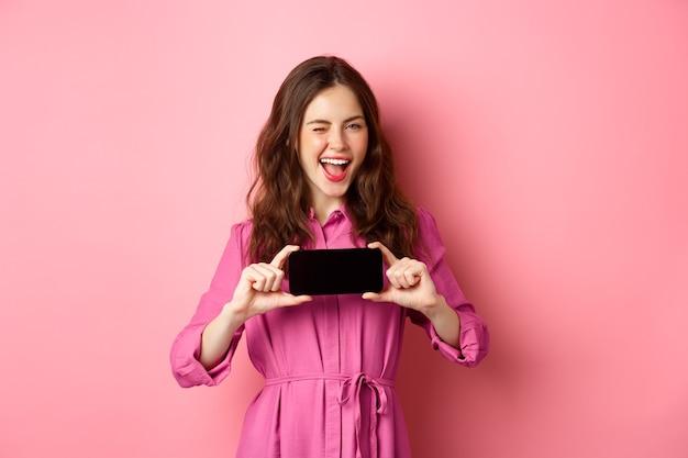 Koncepcja technologii. wesoła dama w sukience mruga do ciebie, uśmiecha się i pokazuje poziomo ekran telefonu komórkowego, stojąc nad różową ścianą.