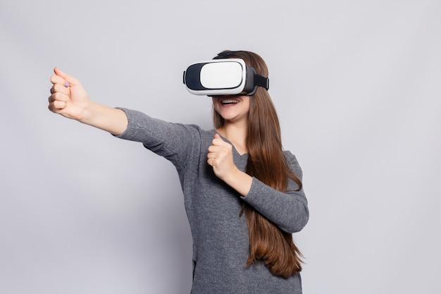 Koncepcja technologii, wirtualnej rzeczywistości, rozrywki i ludzi - szczęśliwa młoda kobieta z zestawem słuchawkowym wirtualnej rzeczywistości lub okularami 3d. kobieta z goglami wirtualnej rzeczywistości. studio strzał, szare tło