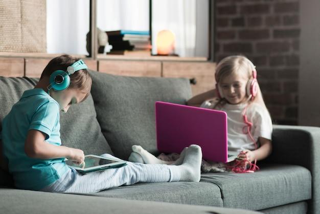 Koncepcja technologii z dwójką dzieci na kanapie