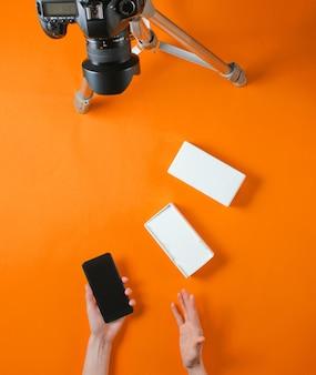 Koncepcja tehnobloger. kobiece ręce rozpakowywanie nowego smartfona z pudełkiem i blogowanie aparatem na statywie na pomarańczowym tle. widok z góry