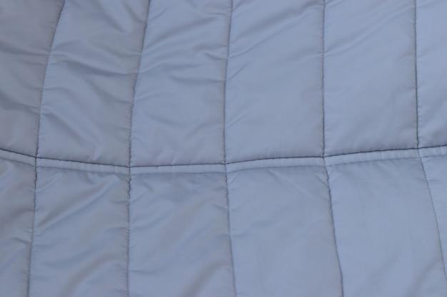 Koncepcja tekstyliów i tekstur - zbliżenie zmiętego szarego srebrnego tła tkaniny