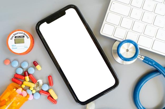 Koncepcja telemedycyny online, stetoskop i pigułki z nowoczesnym telefonem, makieta aplikacji medycznej