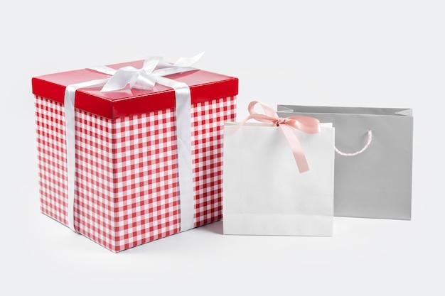 Koncepcja teraźniejszości, prezentów, zakupów i sprzedaży. czerwone pudełko z białą jedwabną kokardką na górze i papierowymi torbami na zakupy na jasnym tle.