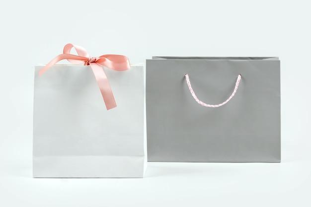 Koncepcja teraźniejszości, prezentów, zakupów i sprzedaży. papierowe torby na zakupy na jasnym tle.