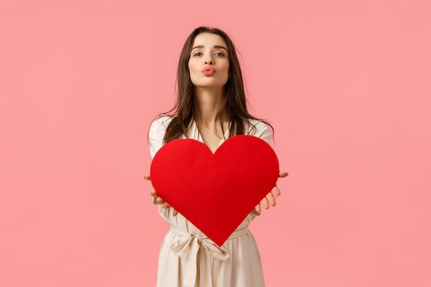 Koncepcja tkliwości, piękna i romansu. atrakcyjna delikatna i zmysłowa młoda kobieta w sukni, składane usta i dmuchanie powietrza pocałunek na aparat jak trzyma karty romantyczny serce, walentynki
