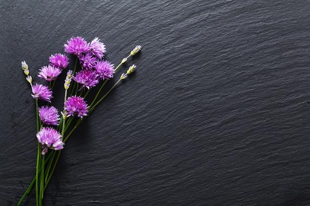 Koncepcja tła dla reklamy żywności lub urody szczypiorkiem kwiatów i aromatycznych ziół na czarnej tablicy łupków z miejsca kopiowania