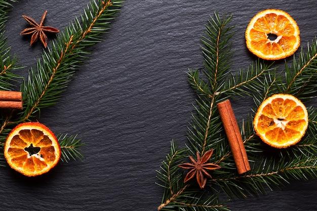 Koncepcja tła sezonowego zimowe lub świąteczne przyprawy i sosna pozostawiają na czarnej płycie łupkowej z miejsca na kopię