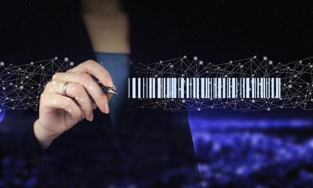 Koncepcja towaru przywieszka z ceną kodów kreskowych. dłoń trzymająca cyfrowy pióro graficzne i rysunek cyfrowy hologram kod kreskowy cena tag znak na ciemnym tle niewyraźne miasta. magazyn i logistyka.