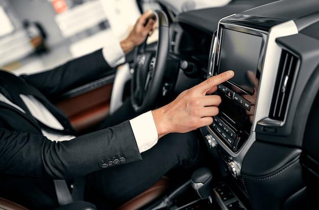 Koncepcja transportu, miejsca docelowego, nowoczesnej technologii i ludzi - męskiej dłoni szukającej trasy za pomocą systemu nawigacji na ekranie deski rozdzielczej samochodu