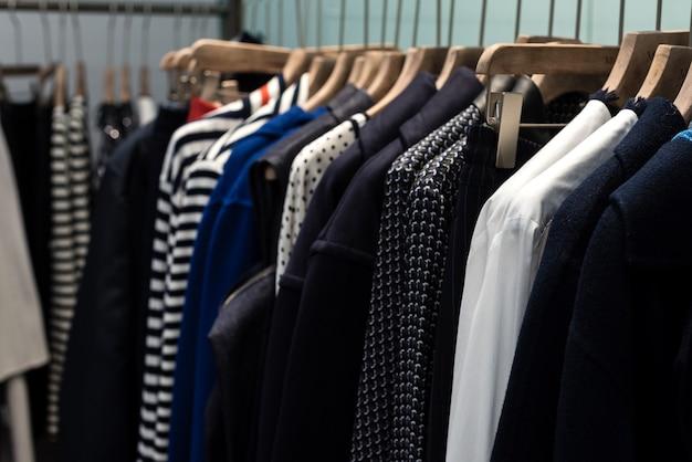 Koncepcja trendu mody. ciepła zimowa kolekcja odzieży damskiej z dzianinowymi wełnianymi sweterkami na drewnianych wieszakach.