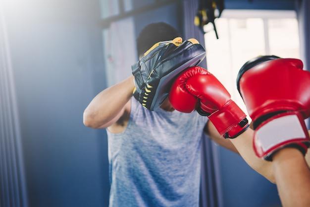 Koncepcja treningu; młody człowiek ćwiczący trening w klasie; młodzi ludzie uprawiający boks i pracę nóg w klasie treningowej