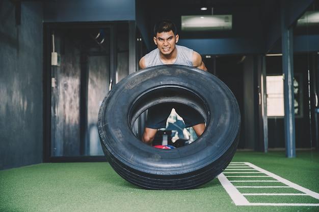 Koncepcja treningu; młody człowiek ćwiczący trening w klasie; uczucie zaangażowania i cierpliwości do podnoszenia ciężarów za pomocą dużych opon