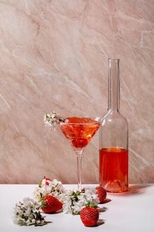 Koncepcja truskawkowego koktajlu alkoholowego lub bezalkoholowego w szklanej butelce martini, ozdobionej kwitnącymi gałęziami wiśni na biało-różowej marmurowej ścianie