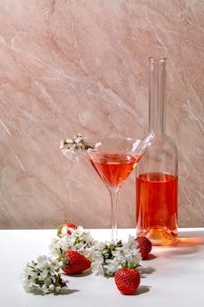 Koncepcja truskawkowego koktajlu alkoholowego lub bezalkoholowego w szkle i szklanej butelki ozdobionej kwitnącymi gałęziami wiśni na biało-różowej marmurowej ścianie