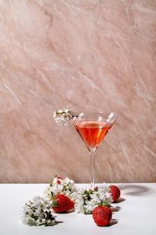 Koncepcja truskawkowego koktajlu alkoholowego lub bezalkoholowego w szkle martini ozdobionym kwitnącymi gałęziami wiśni na białej i różowej ścianie tekstury. skopiuj miejsce