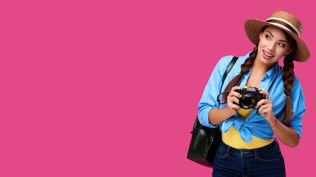 Koncepcja turystyki. szczęśliwy kaukaski kobieta turysta w letniej odzieży na co dzień trzymając aparat fotograficzny, na białym tle na różowym tle z miejsca na kopię
