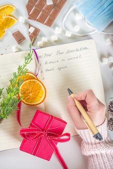 Koncepcja uchwały w sprawie nowego roku pandemii roku 2021. notatnik z celami noworocznymi i rozdzielczością w tle z nowymi normalnymi celami życiowymi, dekoracjami świątecznymi, gorącą czekoladą