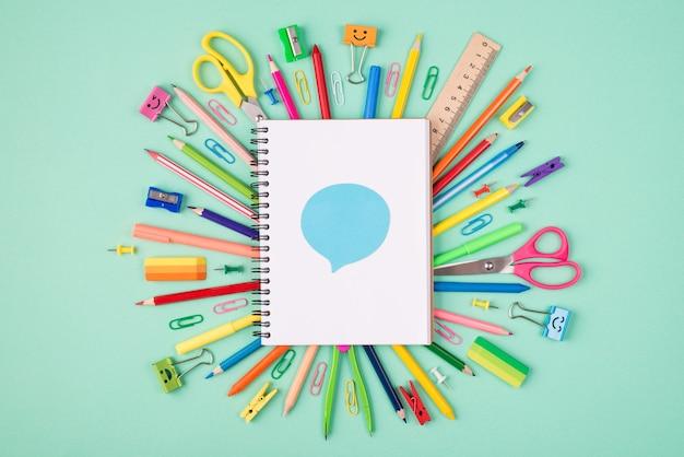 Koncepcja udostępniania pomysłów. widok z góry na zdjęcie kolorowej papeterii i pustego notatnika z niebieską bańką na górze na białym tle na turkusowym tle