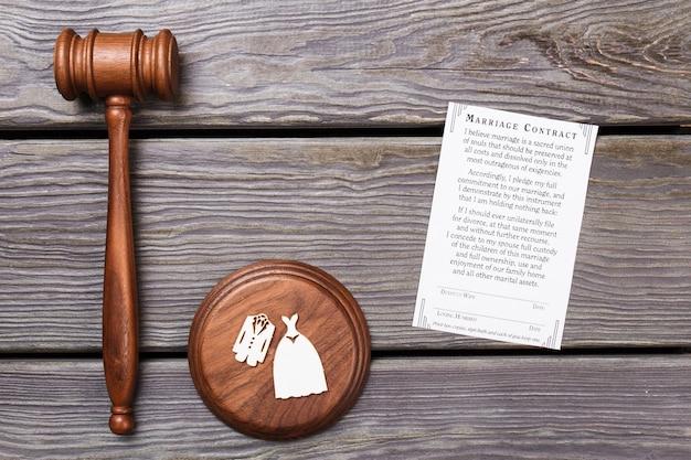 Koncepcja umowy małżeństwa. płaski drewniany młotek z blokiem dźwiękowym, kostiumami ślubnymi i papierem z kontraktem.