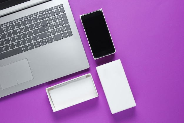 Koncepcja unboxingu, blogowanie techno. pudełko z nowym smartfonem, laptopem na fioletowej powierzchni.