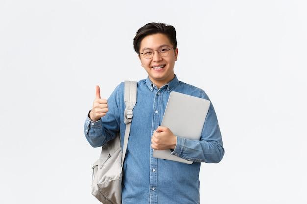 Koncepcja uniwersytetu, studiów za granicą i stylu życia. zadowolony, szczęśliwy azjatycki student płci męskiej w okularach i koszuli pokazujący kciuk w górę z aprobatą, lubi studiować na studiach, trzymając laptopa i plecak.