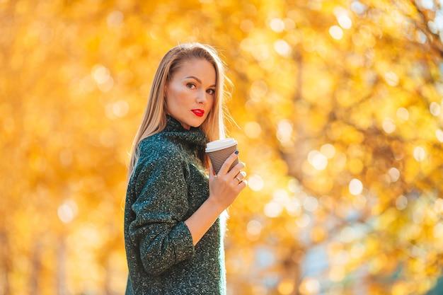 Koncepcja upadku - piękna kobieta w parku jesienią pod liśćmi jesieni
