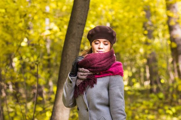 Koncepcja upadku, przyrody i ludzi - młoda piękna kobieta w szarym płaszczu stojąc w parku jesienią.